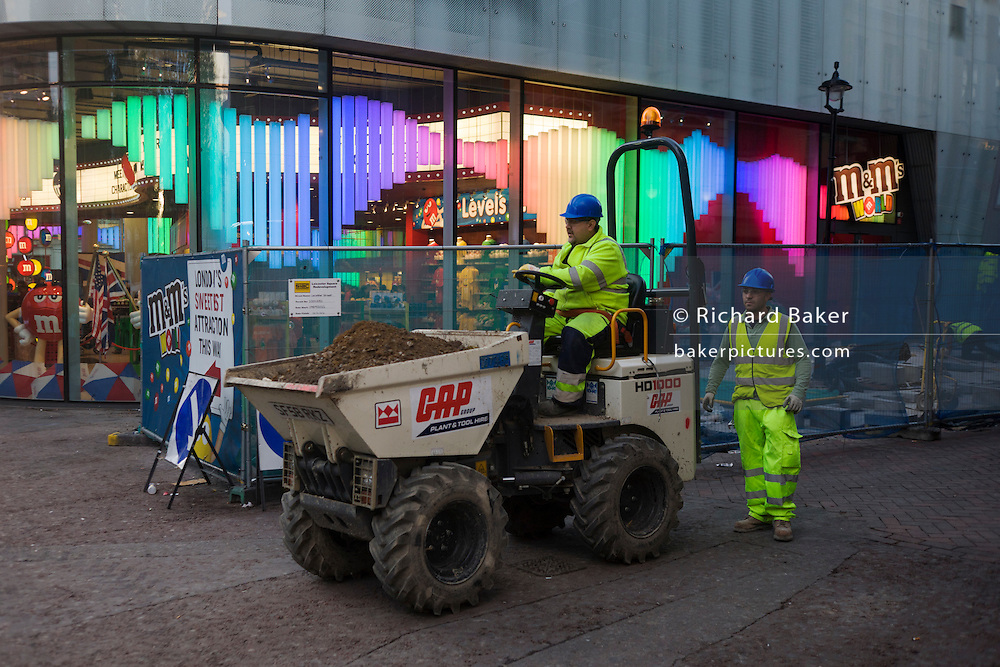 Workmen carefully take a hired dumpster through London's Leicester Square in front the M&Ms retail outlet.