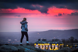 © Licensed to London News Pictures. 18/02/2019. Ilkley UK. A young woman watches the sky turn pink from the top of Ilkley Moor this morning at dawn in Yorkshire. Photo credit: Andrew McCaren/LNP