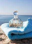 A bottle with seashells on a blue beach towel selective focus on the foreground