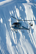 An A-star helicopter flies in front of steep winter mountains near Terrace, BC, Canada.