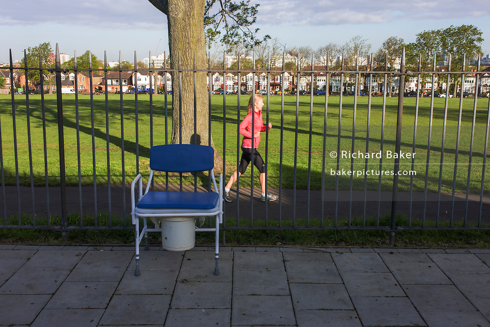 A jogger runs past a dumped commode by the railings of a south London park.
