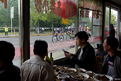 China Chongming Liv lead the peloton past a restaurant packed with diners at Tour of Chongming Island - Stage 1. A 118.8km road race on Chongming Island, China on 5th May 2017.