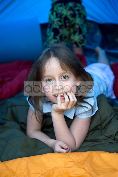 Close up of young girl lying inside tent