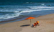 An orange umbrella and two beach chairs are set up facing the ocean in Duck, NC late on the afternoon.
