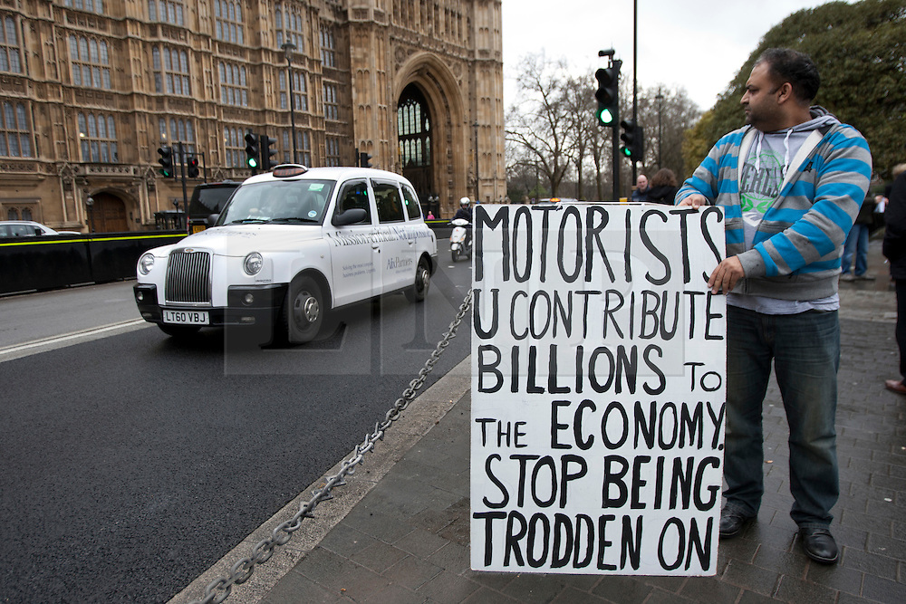 © licensed to London News Pictures. London, UK 07/03/2012. A FairFuel protester stands outside the Houses of the Parliament with a sign as the FairFuel protest group lobby parliament after handing in their report to Downing Street. Photo credit: Tolga Akmen/LNP