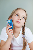 Thoughtful young girl holding credit card over gray background