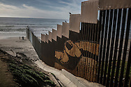 A group of people approach the US-built border wall from the mexico where it extends into the sea at Playas de Tijuana.  Tijuana, Mexico  The US/Mexico border wall has many names south of the border, including El Muro de Verguenza (Wall of Shame) but the most common name I encountered on a recent trip as El Muro de Lágrimas (Wall of Tears).