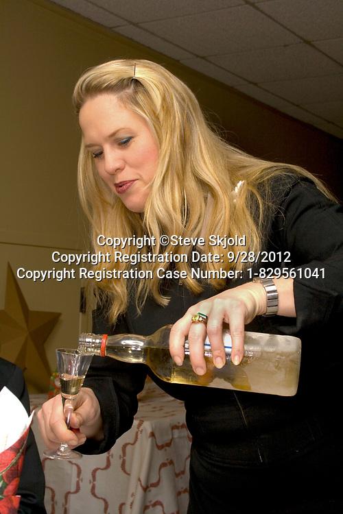 Hostess serving Aquavit liqueur. Annual Swedish Christmas Julbord at the American Swedish Institute Minneapolis Minnesota MN USA