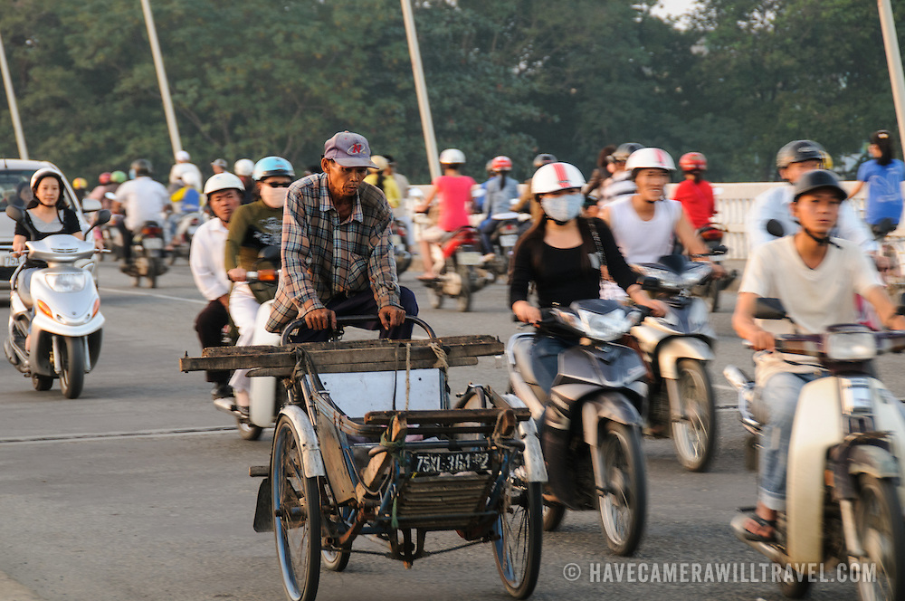 A man rides an old rickshaw bicycle through evening traffic on Cau Phu Xuan in Hue, Vietnam.