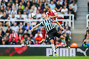 Nacho Monreal (#18) of Arsenal wins the header against Matt Ritchie (#11) of Newcastle United during the Premier League match between Newcastle United and Arsenal at St. James's Park, Newcastle, England on 15 September 2018.