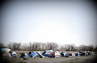 "A homeless encampment or ""tent city"" on the banks of the American River in Sacramento, CA."