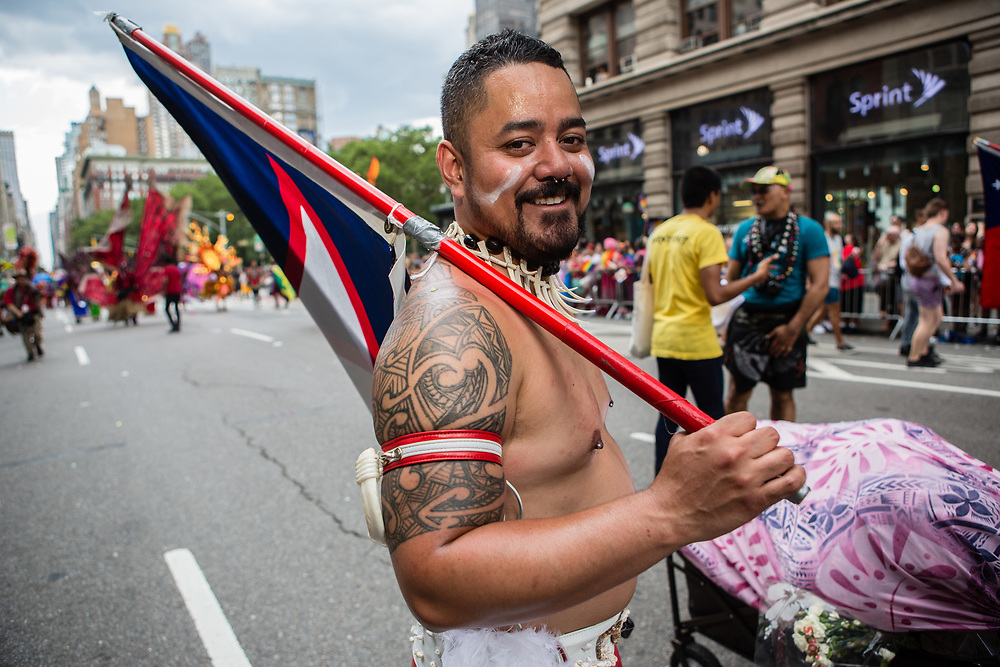 New York, NY - 25 June 2017. New York City Heritage of Pride March filled Fifth Avenue for hours with groups from the LGBT community and it's supporters. A man representing American Samoa marches with U.T.O.P.I.A., the United Territories of Pacific Islanders Alliance.