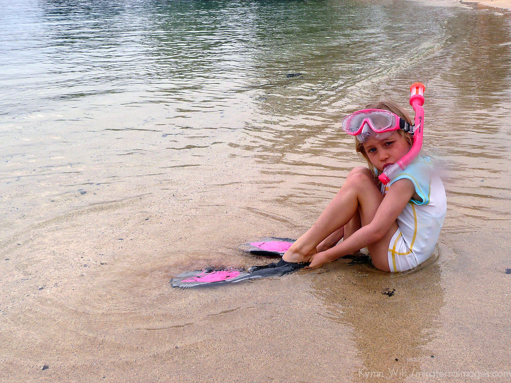 USA, Hawaii, Kohala Coast. Young girl getting ready to snorkel at Hapuna beach. Model-released.