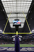 An American flag is displayed on the jumbotron television screen hanging over the football field in this general view photograph taken before the Dallas Cowboys 2017 NFL week 3 preseason football game against the Oakland Raiders, Saturday, Aug. 26, 2017 in Arlington, Tex. The Cowboys won the game 24-20. (©Paul Anthony Spinelli)