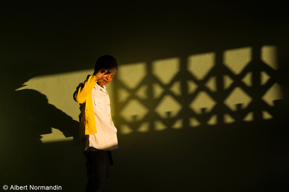 Young boy walks through shadows and light, tips hat to camera, inside temple, Hpa-an