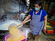 03 FEBRUARY 2019 - BANGKOK, THAILAND: A woman pulls cooked soybeans out of the vat in Bangkok's Chinatown. The soybeans will be used to make desserts and snacks for Chinese New Year. Chinese New Year celebrations in Bangkok start on February 4, 2019. The coming year will be the Year of the Pig in the Chinese zodiac. About 14% of Thais are of Chinese ancestry and Lunar New Year, also called Chinese New Year or Tet is widely celebrated in Chinese communities in Thailand.          PHOTO BY JACK KURTZ