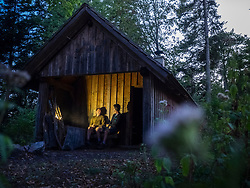 Two male hikers relaxing in front of small hut in Black Forest at night, Baden-Wuerttemerg, Germany