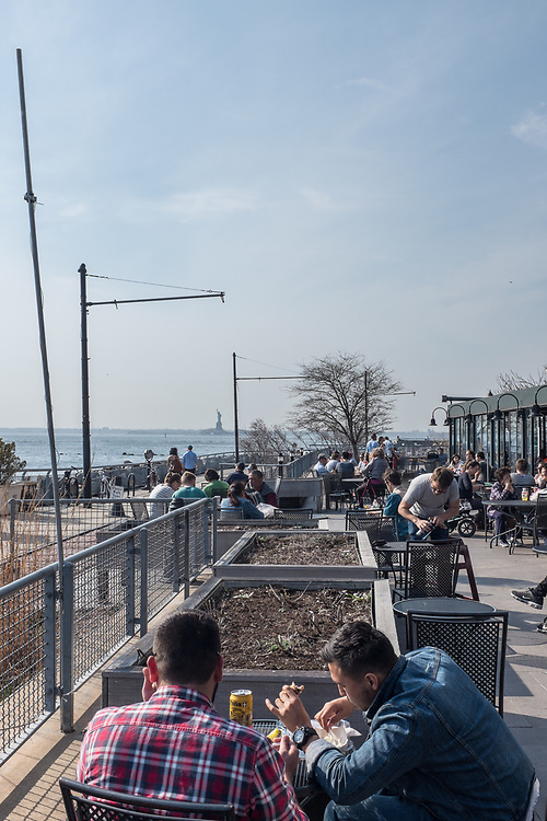 A view of New York Harbor with the Statue of Liberty in the background from the terrace behind the Fairway market in Brooklyn's Red Hook.