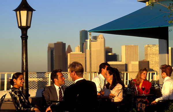 Stock photo of a group of people dining on a rooftop patio after work in downtown Houston Texas