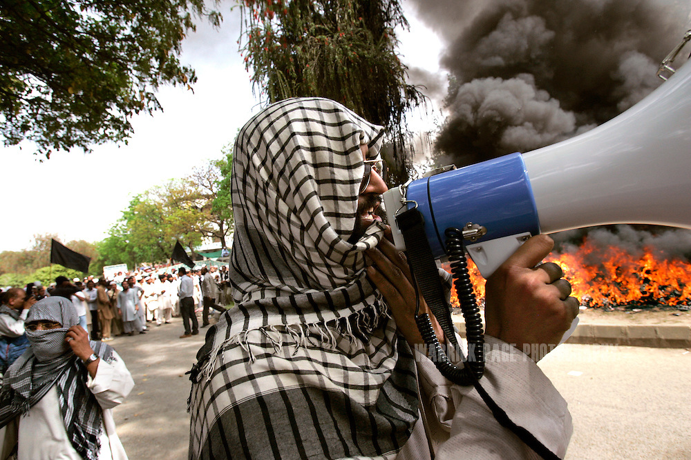 "ISLAMABAD, PAKISTAN - APRIL 6: A religious student of the radical Islamist Red Mosque address the crowd with a loudspeaker while thousands of CDs and DVDs are torched in an ""anti-vice"" drive after Friday prayers in Islamabad, Pakistan, Friday, April 6, 2007. In a siege lasting a week beginning July 3, 2007, Pakistani special forces stormed the madrassa compound on July 10, killing an unknown number of militants and students, with reports varying from 200 to more than 1000 killed. The incident propelled Pakistan into greater turmoil with regular attacks from militant groups against government and military instillations, resulting in terrorist-related deaths numbering more than 800 in 2007. (Photo by Warrick Page)"