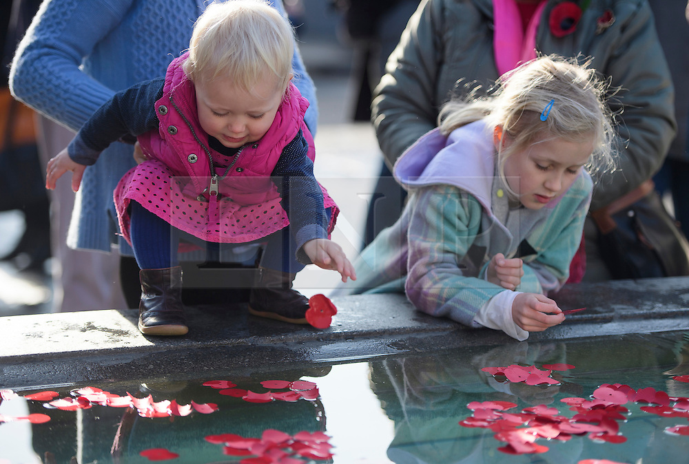 © Licensed to London News Pictures. 11/11/2016. London, UK. Lexi Vanderput, aged one, and her sister Jemila , aged seven (correct spellings) places a poppy in to the fountain during Silence in the Square, a service held in Trafalgar Square, London to mark Remembrance Day. A minutes silence is held on the 11th hour of the 11th day of the 11th month, to recall the end of hostilities of World War I.  Photo credit: Ben Cawthra/LNP