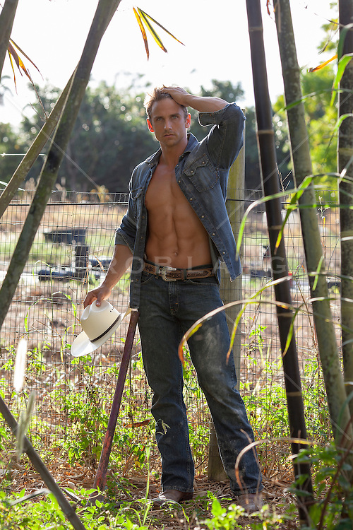 cowboy with an open shirt holding a cowboy hat while standing on a farm with bamboo
