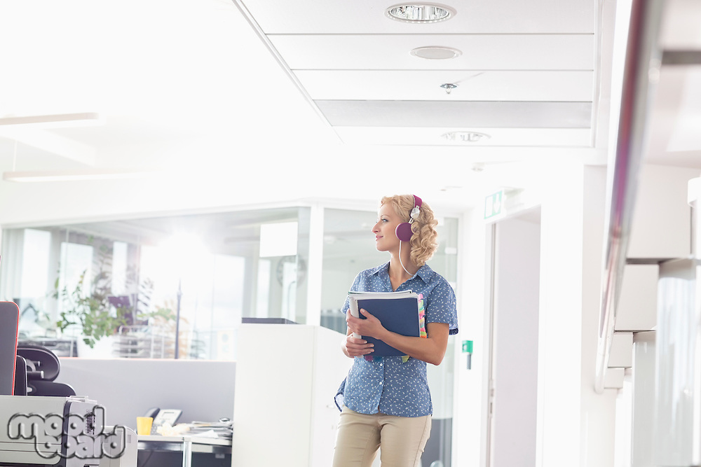 Businesswoman holding files while listening music in creative office