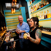 ORLANDO, FL -- Bartender Sheena Cuccia and owner Tyler Brassil share a laugh as they mix whiskey drinks at The Pharmacy in Orlando, Florida.  (PHOTO / Chip Litherland)