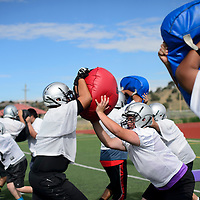 Football players take turns practicing defensive and offensive skills on bags at Miyamura High School football practice in Gallup Monday.