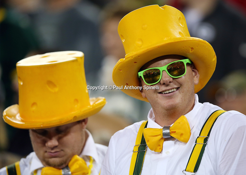 A pair of Green Bay Packers fans wear cheese head hats during the Green Bay Packers 2015 NFL week 3 regular season football game against the Kansas City Chiefs on Monday, Sept. 28, 2015 in Green Bay, Wis. The Packers won the game 38-28. (©Paul Anthony Spinelli)