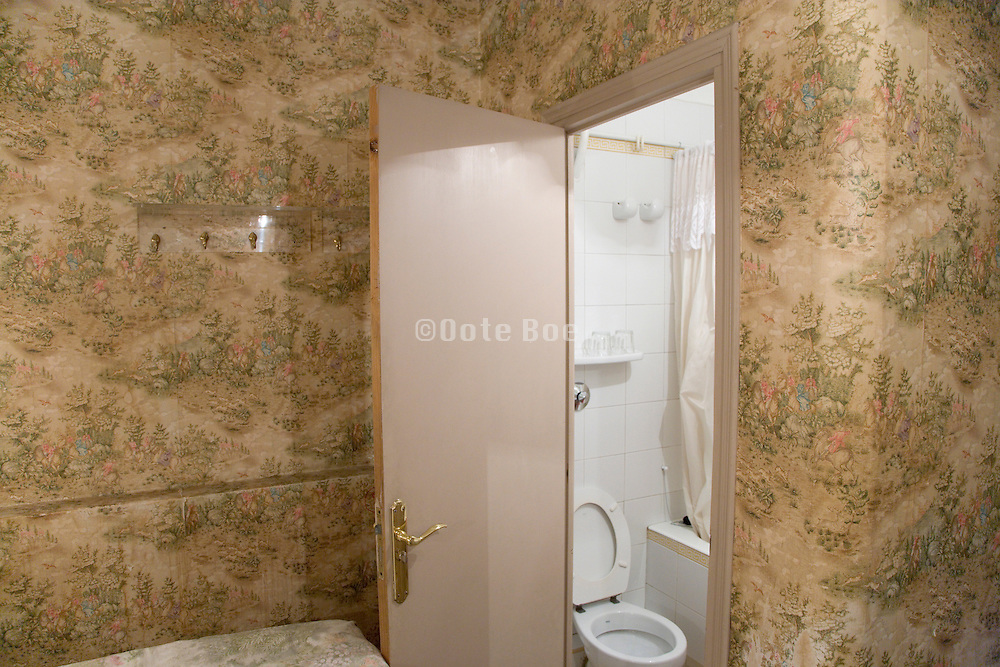a small hotel room with door to the toilet at end of bed