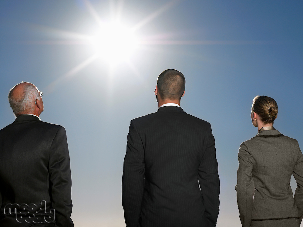 Rear view of three business people in suits looking up at the sun for inspiration