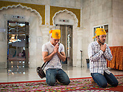 "08 FEBRUARY 2015  BANGKOK, THAILAND: Sikh men in the Darbar Sahib (prayer hall) at Gurdwara Siri Guru Singh Sabha, the Sikh temple in Bangkok. Thailand has a small but influential Sikh community. Sikhs started coming to Thailand, then Siam, in the 1890s. There are now several thousand Thai-Indian Sikh families. Gurdwara Siri Guru Singh Sabha was established in 1913. Construction of the current building, adjacent to the original Gurdwara (""Gateway to the Guru""), started in 1979 and was finished in 1981. The Sikh community serves a daily free vegetarian meal at the Gurdwara that is available to people of any faith and background.    PHOTO BY JACK KURTZ"