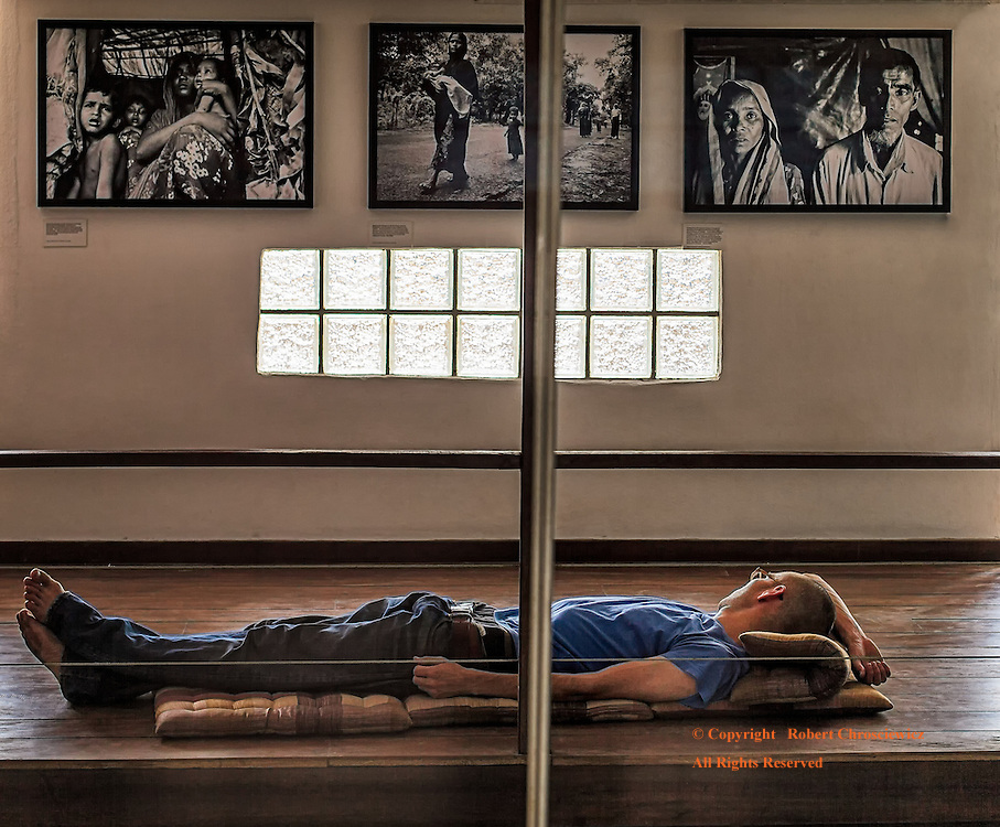 Whose Looking at Who?: A Caucasian man relaxes in a gallery, gazing at three photographs of coloured people trapped within the insurmountable social and economic barriers of a far removed existence, Chaing Mai Photo Club, Chiang Mai Thailand.