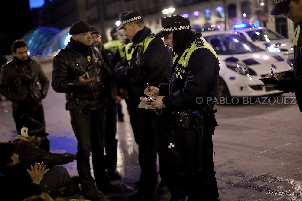 Police checks demonstrators identities on the first night of a camp protest in Puerta del Sol Square after a demonstration against alleged corruption scandals implicating the PP (Popular Party) on February 4, 2013 in Madrid, Spain. Spain's Prime Minister Mariano Rajoy yesterday denied receiving undeclared payments from his political party. More information on secret payments were revealed today and leader of opposition socialist Party (PSOE) urged Rajoy to resign.