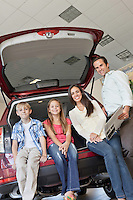 Portrait of happy family sitting at back of their new car
