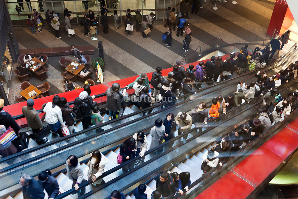 overhead view of escalator with people at Queen's Square building in Yokohama Japan