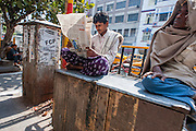 Man reading newspaper in Kolkata street (India).