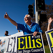 District 1 City Council candidate Ray Ellis waves signs off Del Mar Heights Road on Tuesday morning.