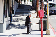 Een oudere man wacht op de stoep in Japan Town in San Francisco. De Amerikaanse stad San Francisco aan de westkust is een van de grootste steden in Amerika en kenmerkt zich door de steile heuvels in de stad.<br /> <br /> An elderly woman stands at the pavement in Japan Town in San Francisco. The US city of San Francisco on the west coast is one of the largest cities in America and is characterized by the steep hills in the city.