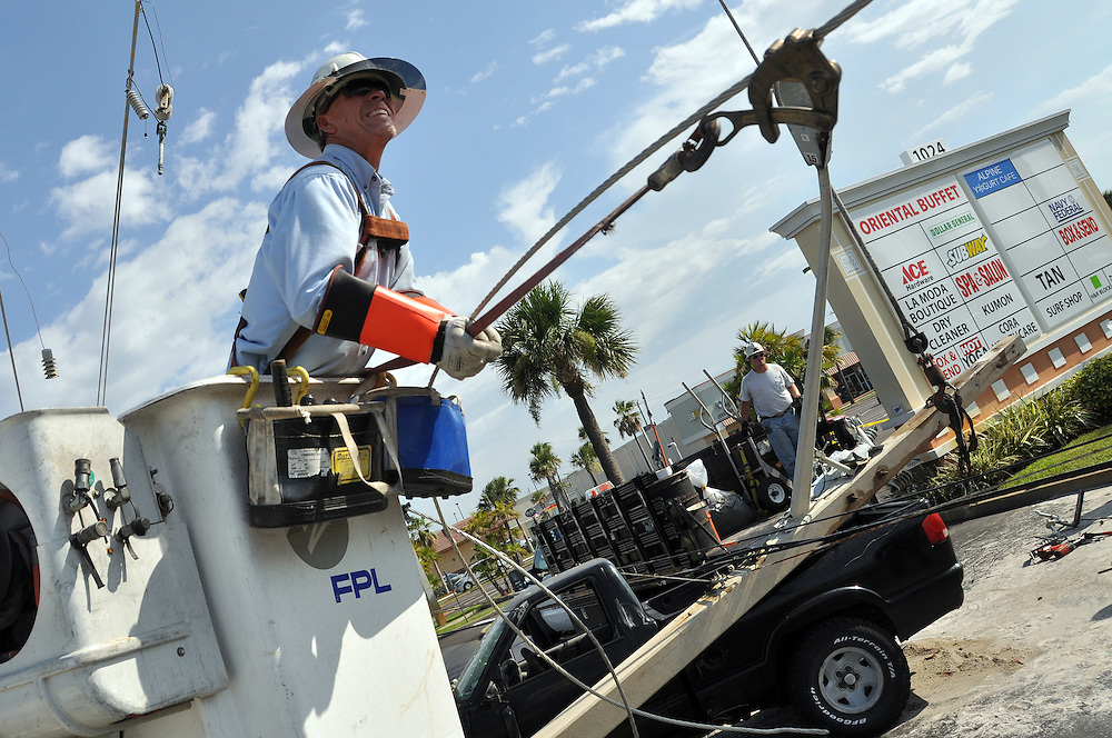 Andrew Knapp, FLORIDA TODAY -- July 13, 2011 -- Florida Power & Light workers begin efforts to restore power Wednesday afternoon after a pickup veered off State Road A1A and crashed into a utility pole in front of the Publix store in Satellite Beach.