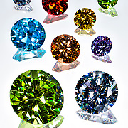 Colorful gemstones cut in diamonds shape on white reflective background