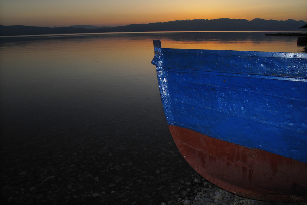 Sunset over Lake Ohrid, Macedonia and the Mokra Pl mountain range in Albania. Fishing boat in foreground. View west across Lake Ohrid from Lagadin area Galicica National Park. Lake Ohrid (693m).<br /> Galicica National Park, Macedonia, June 2009<br /> Mission: Macedonia, Lake Macro Prespa /  Lake Ohrid, Transnational Park<br /> David Maitland / Wild Wonders of Europe