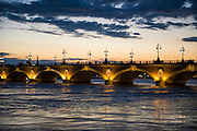Historic bridge Pont de Pierre over the Garonne river at sunset, Bordeaux, France