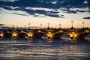 Historic bridge Pont de Pierre over the Garonne river at sunset, Bordeaux, France