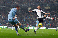 Football - Premier League - Manchester City vs. Fulham<br /> Fulham's Chris Baird attempts to block a cross from Adam Johnson of Manchester City at the Etihad Stadium