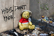 "Winnie the Pooh stuffed bear surrounded by trash while sitting against a chain-link fence and concert wall with ""Kids Dont Know"" spray above the yellow teddy bear."