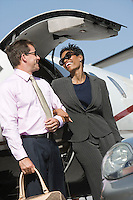 Mid-adult businesswoman and businessman getting of airplane.