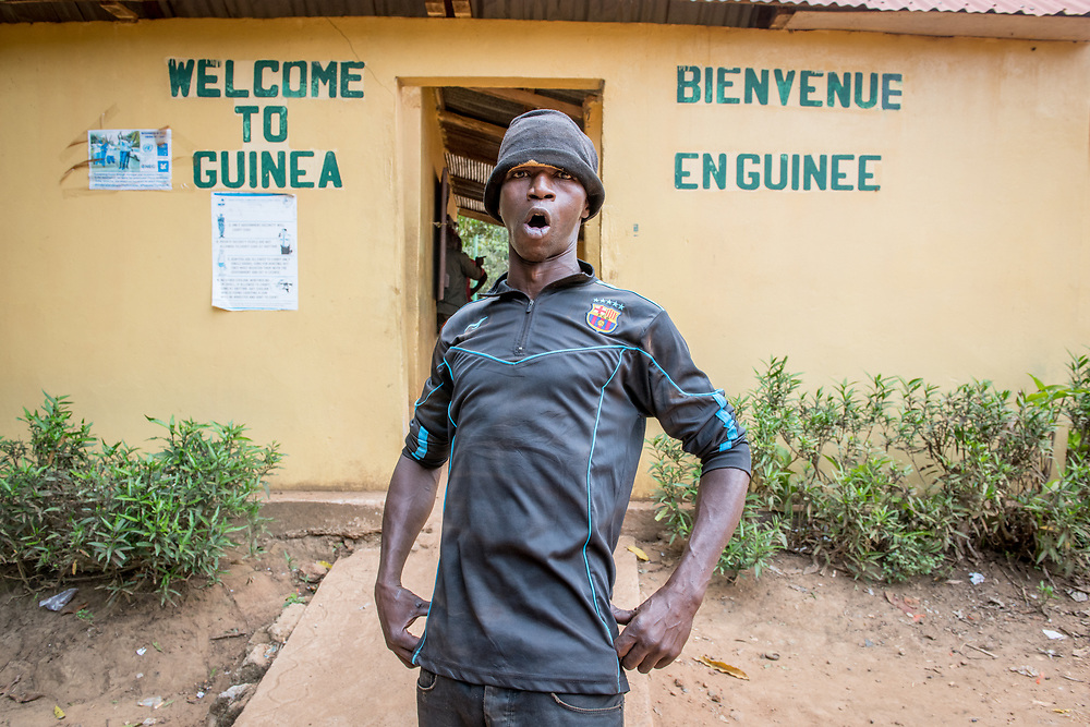 Adult African male stands in powerful stance with mouth agape in front of  Republic of Guinea border crossing