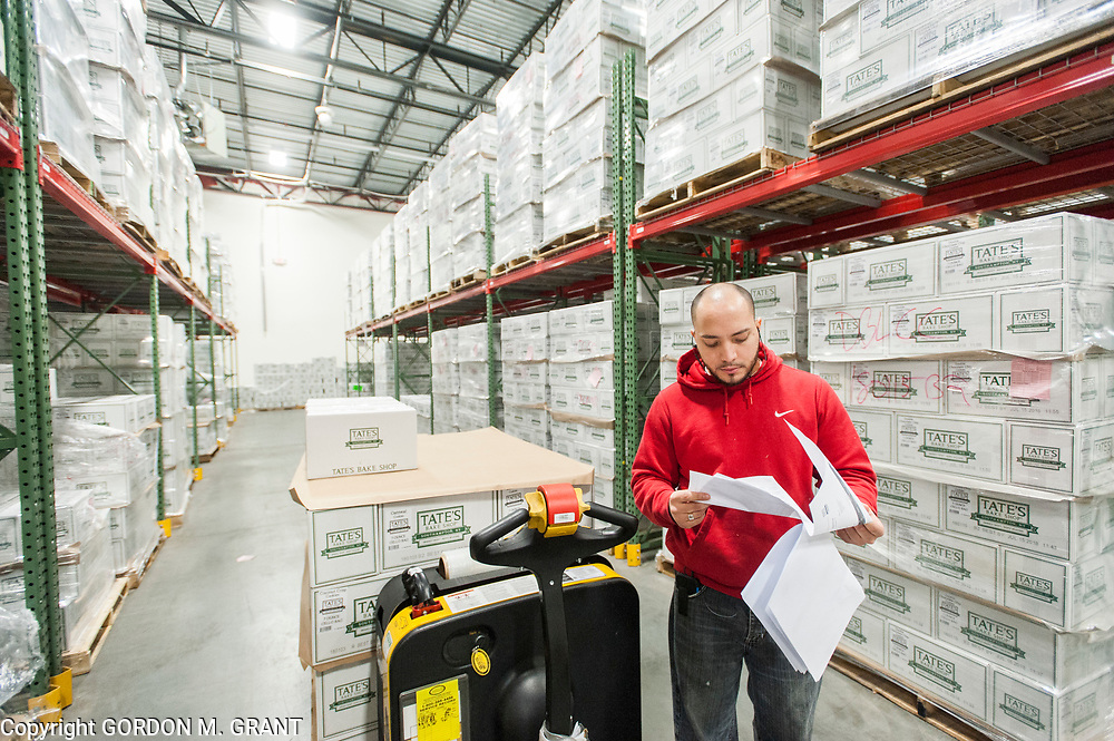 Gil Sanchez fills an order at the Tate's Bake Shop distribution center at the Hampton Business District at Gabreski Airport in Westhampton, Jan. 16, 2018. Tate's Bake Shop is expanding it's distribution facility into a newly constructed building at the site.